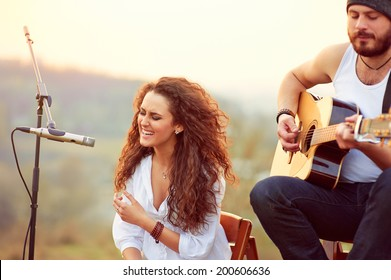 Young beautiful girl singing with a guitar player.