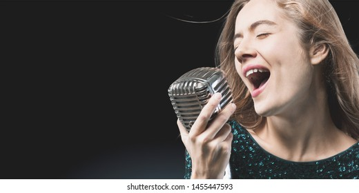 Young beautiful girl singing into a microphone on dark background