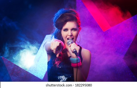 Young beautiful girl singing on stage with star on background.