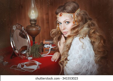 Young beautiful girl sits near a fortune teller desk with a lamp and candles. Card reading. Divination