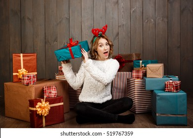 Young beautiful girl sitting among christmas gifts over wooden background.