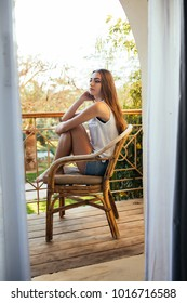 Young beautiful girl sitting on a chair on the balcony of the hotel and looks into the distance.