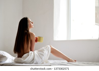 Young beautiful girl sitting on a white bed with a cup in her hand. Across from the window