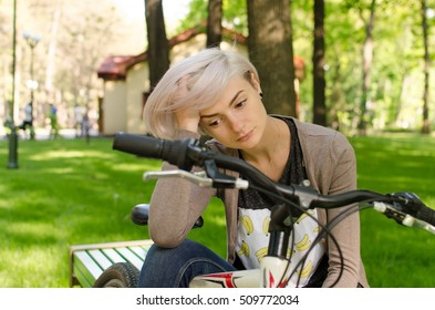Young beautiful girl sitting on the bench near the white bicycle in the park