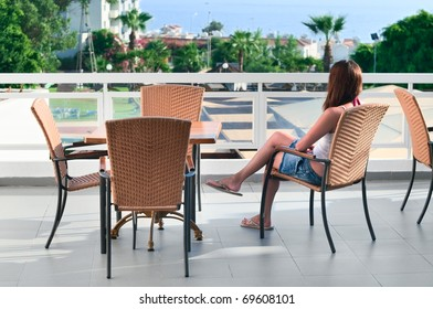 Young beautiful girl sitting on a chair on the balcony of the hotel and looks into the distance. One Caucasian woman is back side