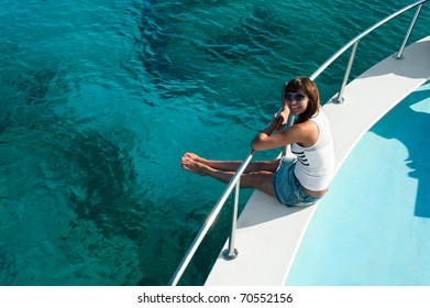 Young beautiful girl sitting on a yacht with his legs hanging in the blue sea