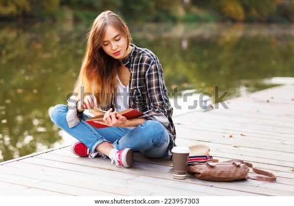 桟橋に座っている若い美しい女の子