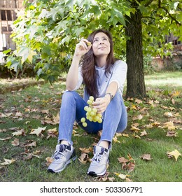 young beautiful girl sitting under a tree eating grapes