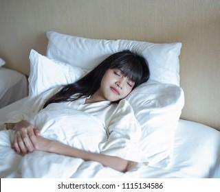 Young beautiful girl sleeping happily on her bed