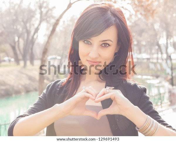 Young beautiful girl smile with hands form heart shape gesture. Photo taken outside, with real sun light as backlight and real lens flares