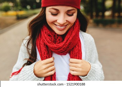 Young beautiful girl smiles laughing outdoors in a red hat and scarf gray cardigan sunset sun , energetic mixed race Caucasian young woman.