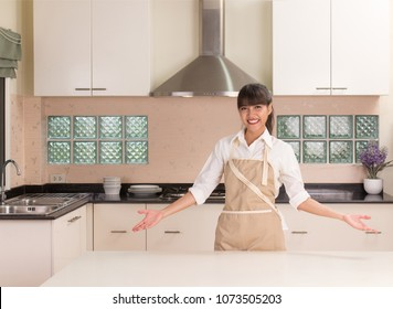 Young beautiful girl smiling  in front of the modern style kitchen