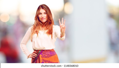 young beautiful girl smiling and looking satisfied and happy, counting number three with fingers.