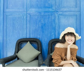 Young beautiful girl smiling and relaxing in front of the blue background