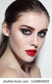 Young beautiful girl with smoky eye makeup and red lips