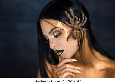 Young beautiful girl with a spider. Spider bird on a beautiful face of a girl. Gold paint on the body. Golden skin. Spider bird on the model's body