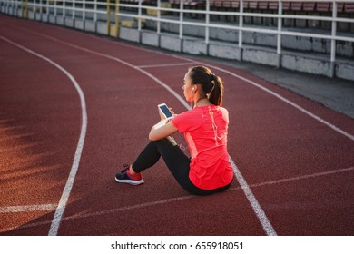 Young, beautiful girl sportsman in sportswear sitting on a treadmill at the stadium with a mobile phone in hands