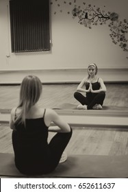 Young beautiful girl in sportswear sitting on the Mat in the gym tucked under her and meditates. Sepia