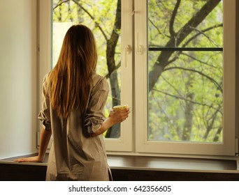 Young beautiful girl stand in a shirt near the window sill early in the morning with a cup of coffee in hand and looking out the window at the street