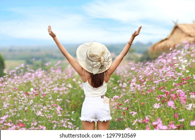 young and beautiful girl standing and raising her arms in the midst of cosmos flowers filed and put cell phone in the back pocket jean (rest time on vacation concept)