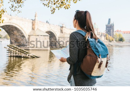 aaec75b97e9b A young beautiful girl stands and looks at the map next to the Vltava River  with
