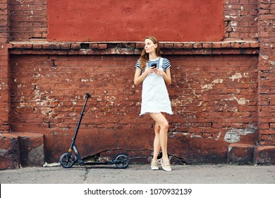 Young beautiful girl stands near a red brick wall in summer in the city and is talking on the phone next to a scooter. The concept of a healthy lifestyle
