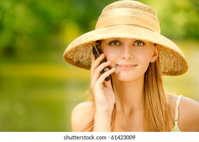 Young beautiful girl in straw hat against lake in city park speaks by mobile phone.
