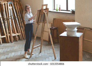 Young beautiful girl student is drawing a Doric capital with a pencil on a wooden easel as her university assignment in a studio