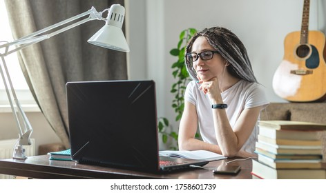 A young beautiful girl student with dreadlocks is studying at an online lesson at home on a laptop. Concept of distance education and exams