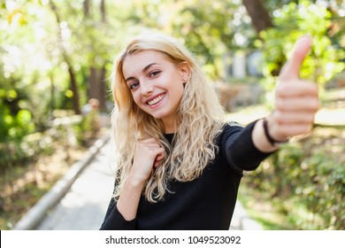 Young beautiful girl student outdoors at street walking in park at a sunny day wearing smart casual simple and modest outfit showing thumbs up