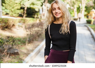 Young beautiful girl student outdoors at street walking in park at a sunny day wearing smart casual simple and modest outfit. Representing generation Z