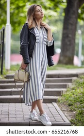 Young beautiful girl in stylish streetwear black leather jacket long striped dress white sneakers and with a fashionable bag strolling in summer city park