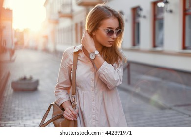 Young beautiful girl in stylish sunglasses and with a fashionable bag at sunset.