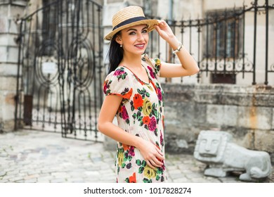 young beautiful girl in summer dress, straw hat. Travels around the European city in the summer. Cheerful, smiling lady. old houses, paving stones, vintage style, old Europe