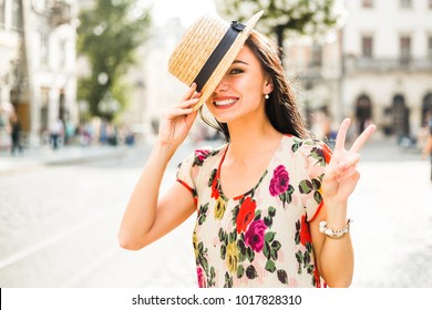 young beautiful girl in summer dress, straw hat. Travels around the European city in the summer. A cheerful, smiling lady shows a sign of victory. old houses, paving stones, vintage style, old Europe