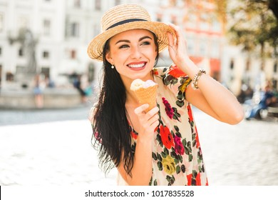 Young beautiful girl in summer dress, straw hat. Travels around the European city in the summer. A cheerful, smiling lady holds ice cream in her hands. Ancient houses, paving stones old Europe