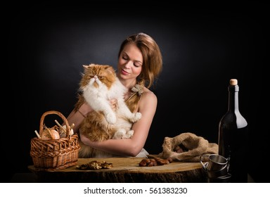 The young beautiful girl in a sundress from  canvas sits at an oak table with   remarkable red Persian cat on hands near  basket  onions , dried mushrooms and  bag  chestnuts