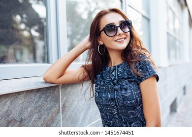 Young beautiful girl in sunglasses posing in the background of a building in the city