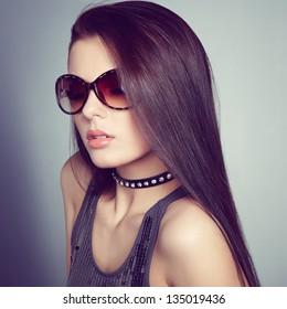 Young beautiful girl in sunglasses. Pretty model poses at studio.