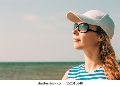 Young beautiful girl with sunglasses resting on the sea.