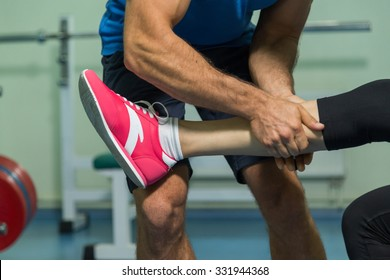Young beautiful girl takes exercises with a trainer. Training in the gym. Proper exercise. Photos for sporting magazines and websites.