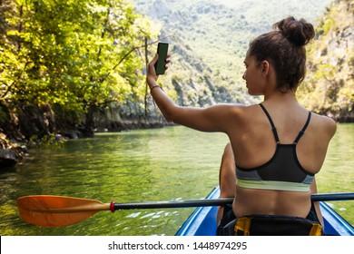young beautiful girl taking a selfy on a kayak ride
