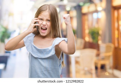 Young beautiful girl talking on the phone over isolated background annoyed and frustrated shouting with anger, crazy and yelling with raised hand, anger concept
