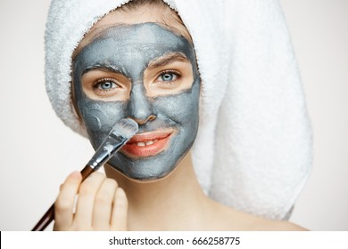 Young beautiful girl in towel on head covering face with mask smiling looking at camera over white background. Beauty cosmetology and spa.