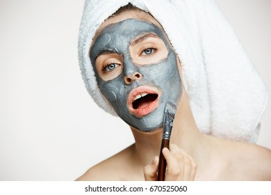 Young beautiful girl in towel on head covering face with mask looking at camera with opened mouth over white background. Beauty cosmetology and spa.