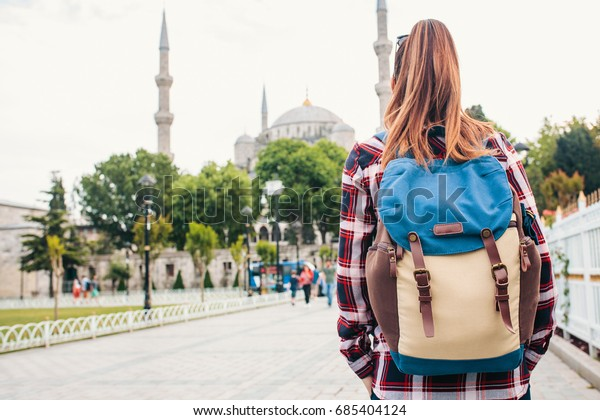 Young beautiful girl traveler with a backpack looking at a blue mosque - a famous tourist attraction of Istanbul. Travel, tourism, sightseeing.