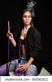 Young, beautiful girl in trendy club clothes and perfect make up smoke a hookah. The pleasure of smoking. Sexy smoke