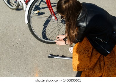 Young beautiful girl trying to pump up the wheel of the bike. A girl holds a pump in her hands and tries to pump up the bike's camera. The girl repairs a bicycle on the street. Bike breakdown