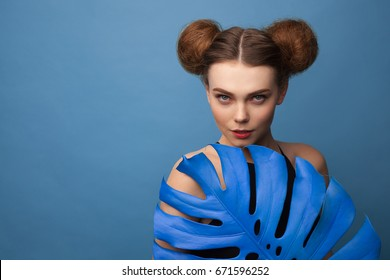 Young beautiful girl with two hair buns holding big blue Monstera leaf and looking at camera.