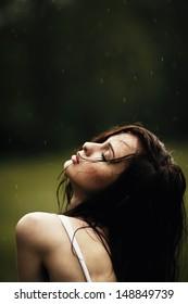 Young beautiful girl under summer rain